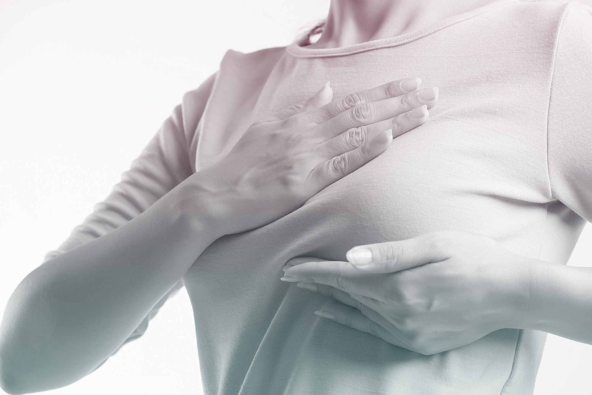 Midsection Of Woman Examining Breast While Standing Against White Background