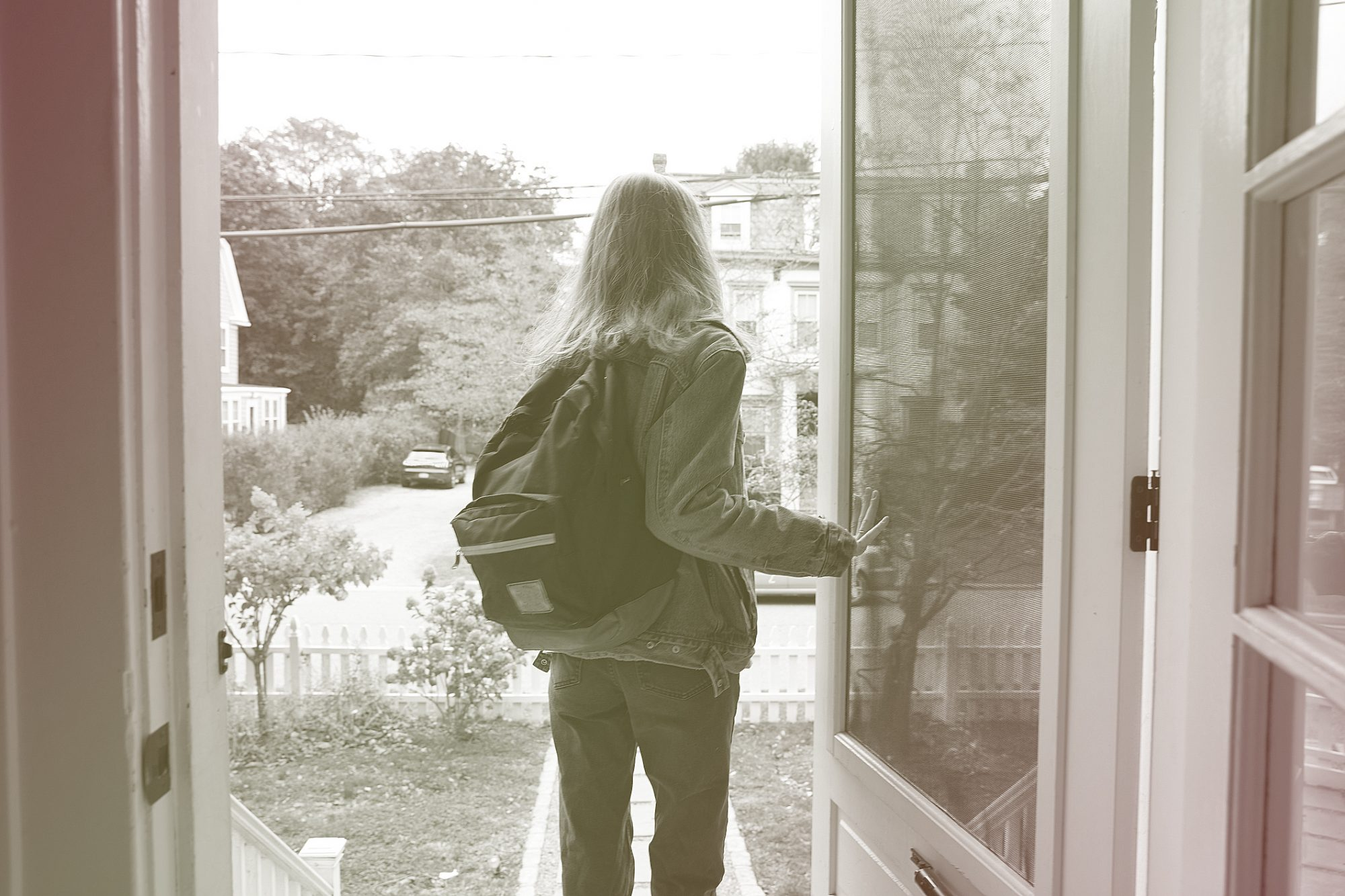 Back view of teenage girl walking out the front door of her house