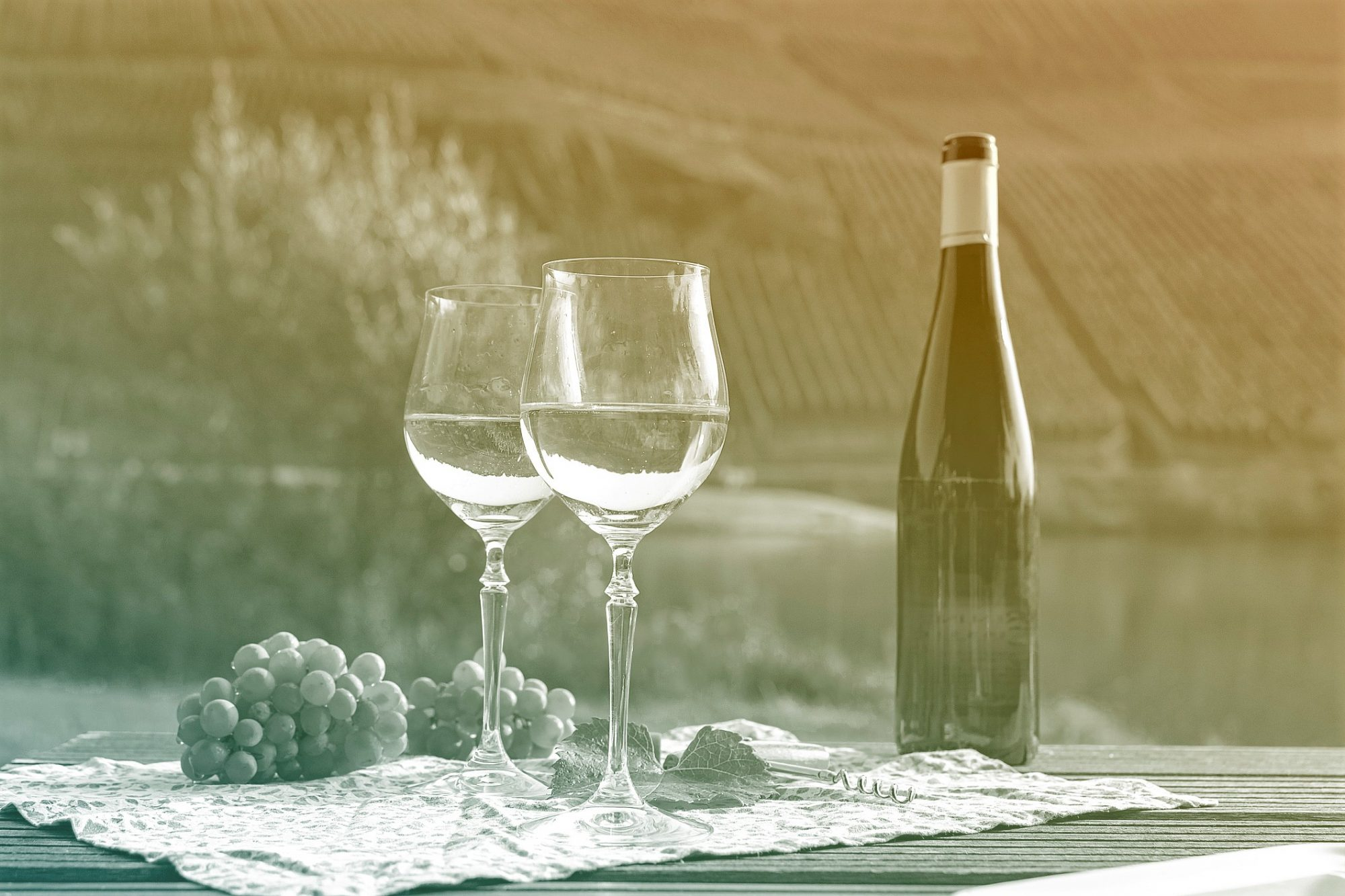 wine bottle, wine glasses, and grapes on table outside