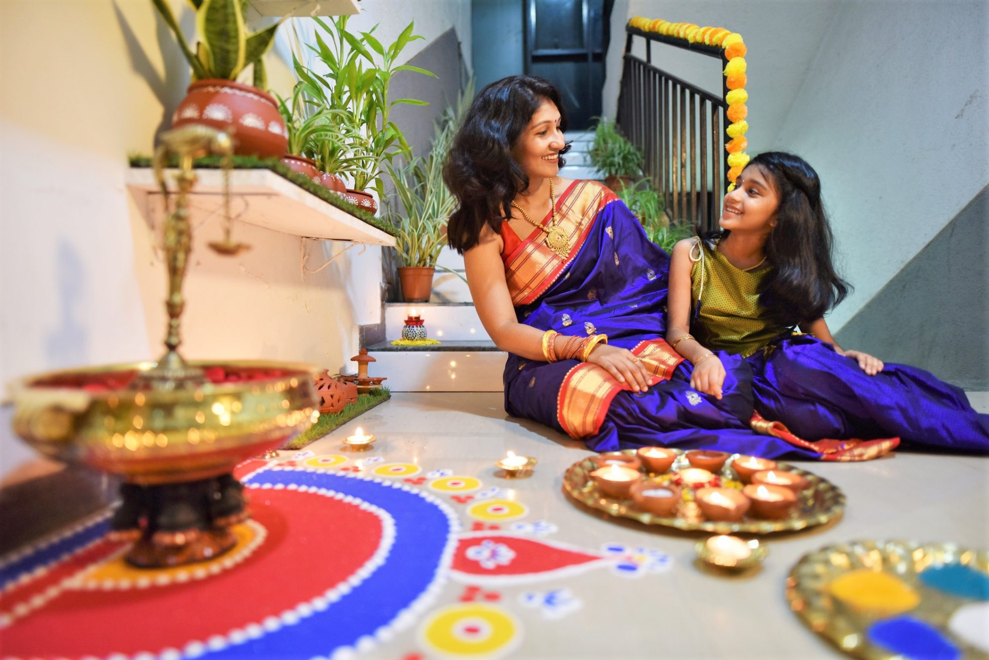 Indian woman and her daughter dressed in traditional wear decorating house with rangoli and oil lamps