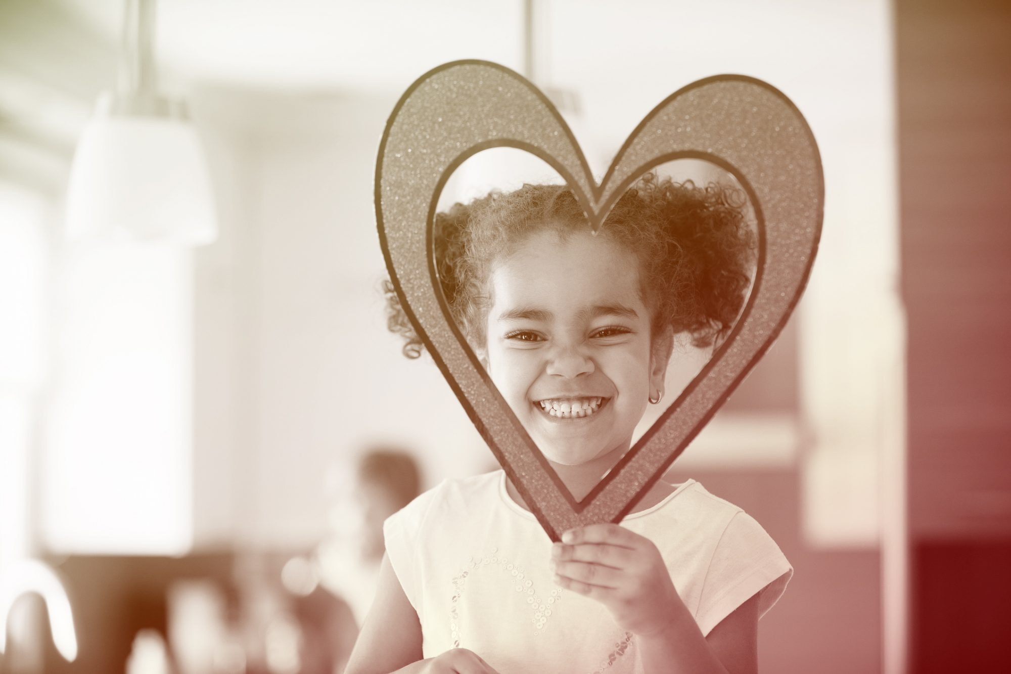 child holding a cut-out of a heart over her face