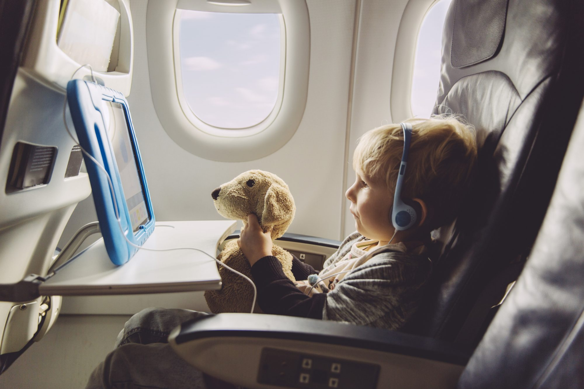 Little boy sitting on an airplane wearing headphones watching something on digital tablet