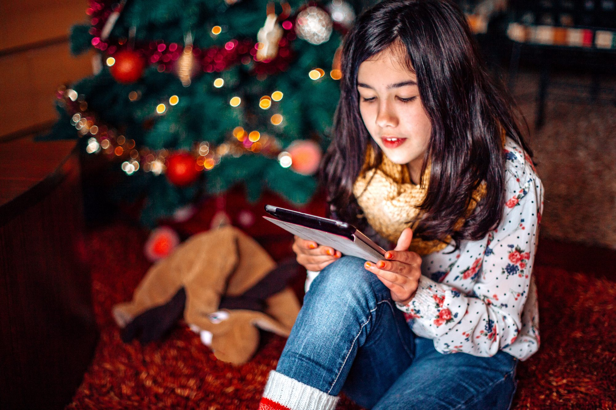 A photo of a young girl on her iPad during Christmas time.