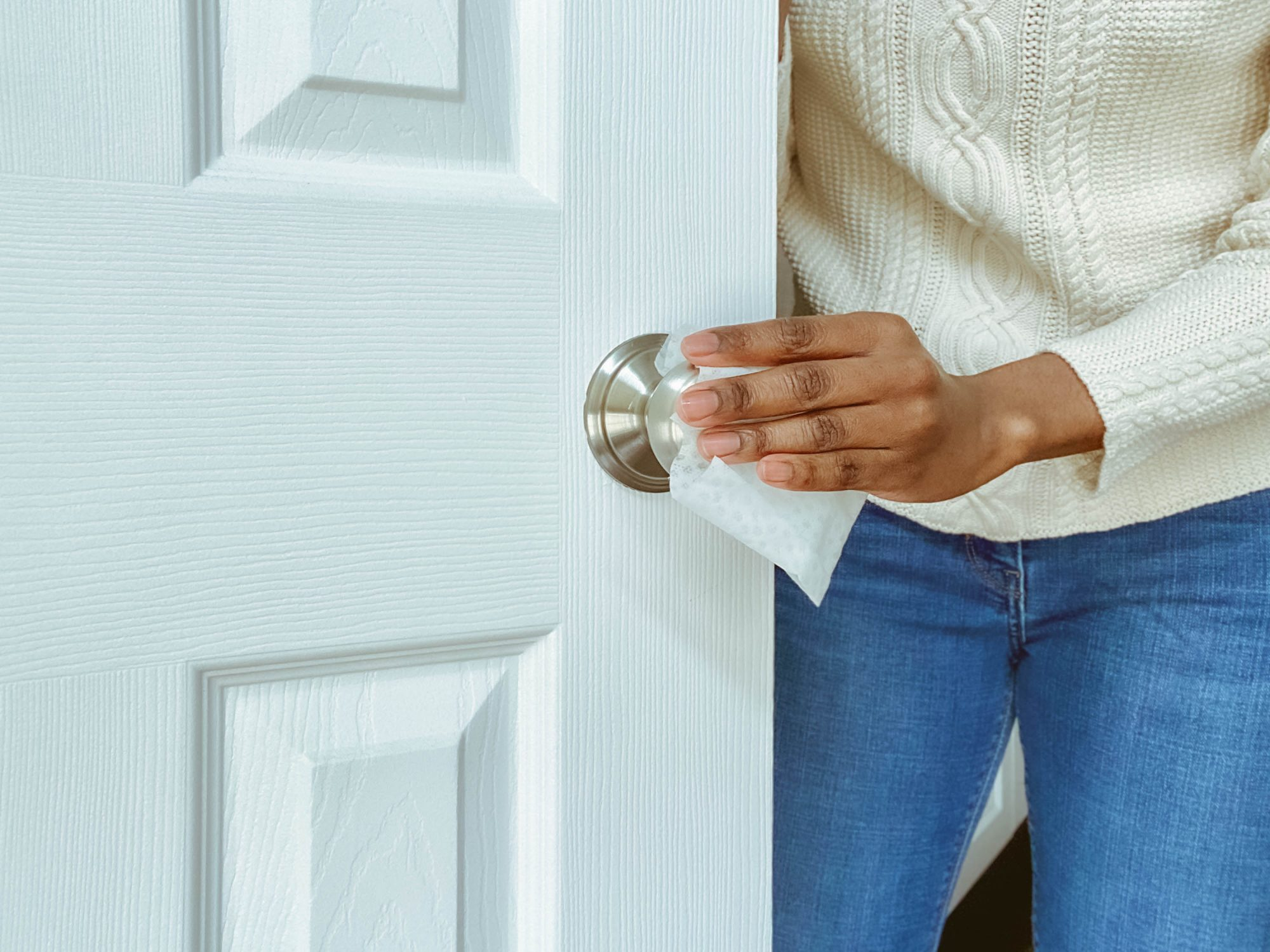An image of a woman cleaning a doorknob using a disinfecting wipe.