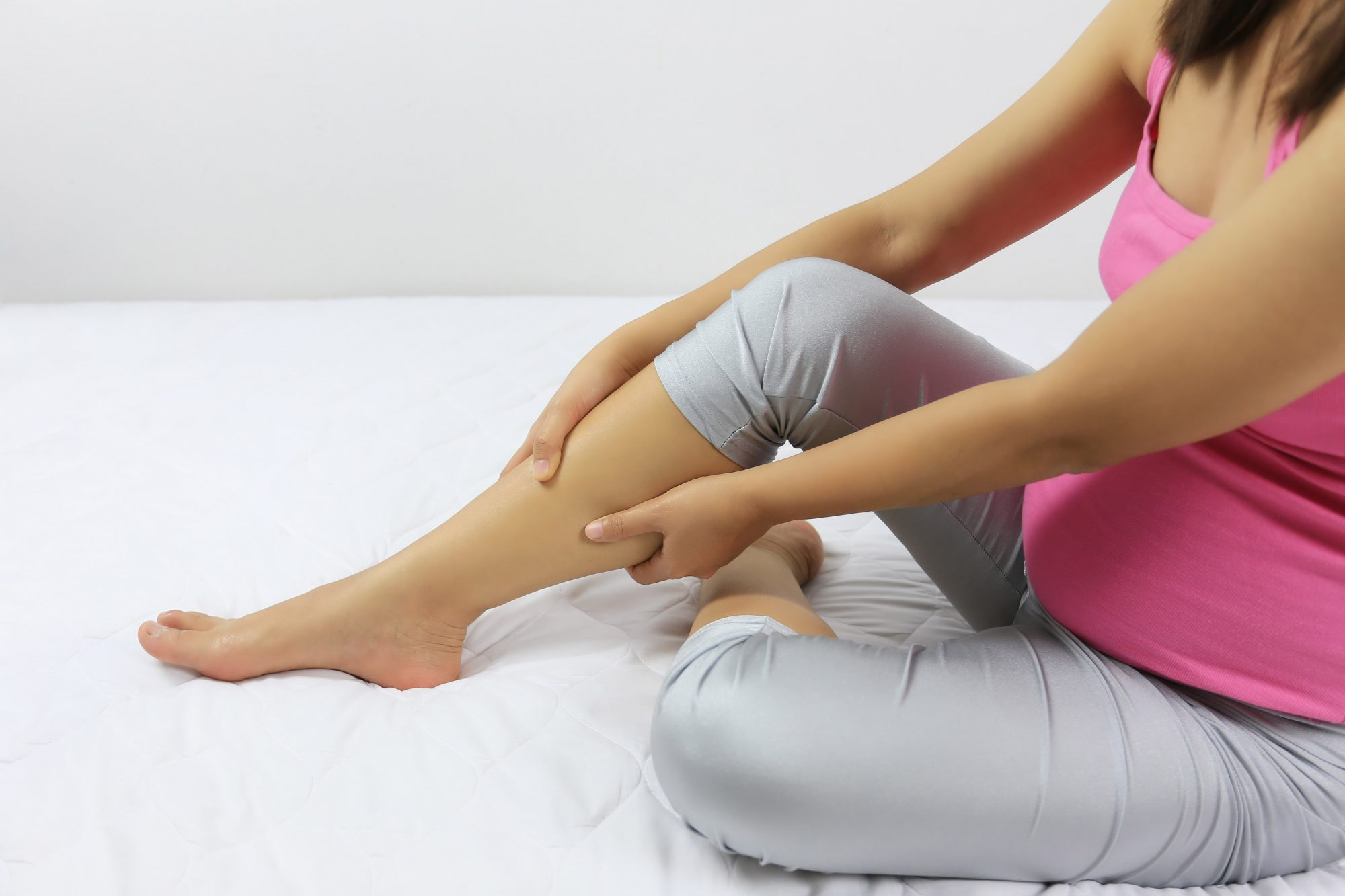 An image of a pregnant woman holding her leg.