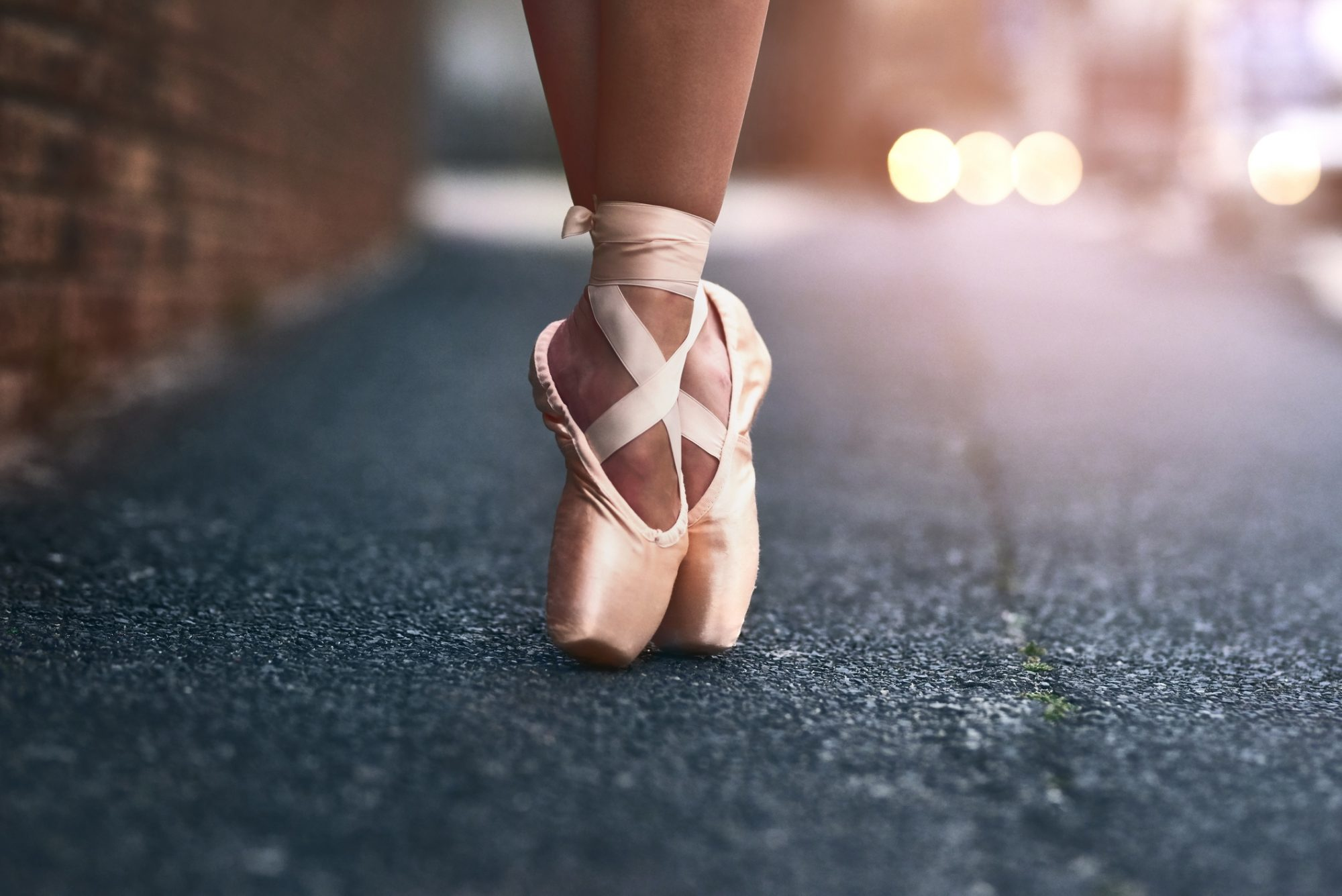 Cropped shot of a ballet dancer standing on tiptoes against an urban background
