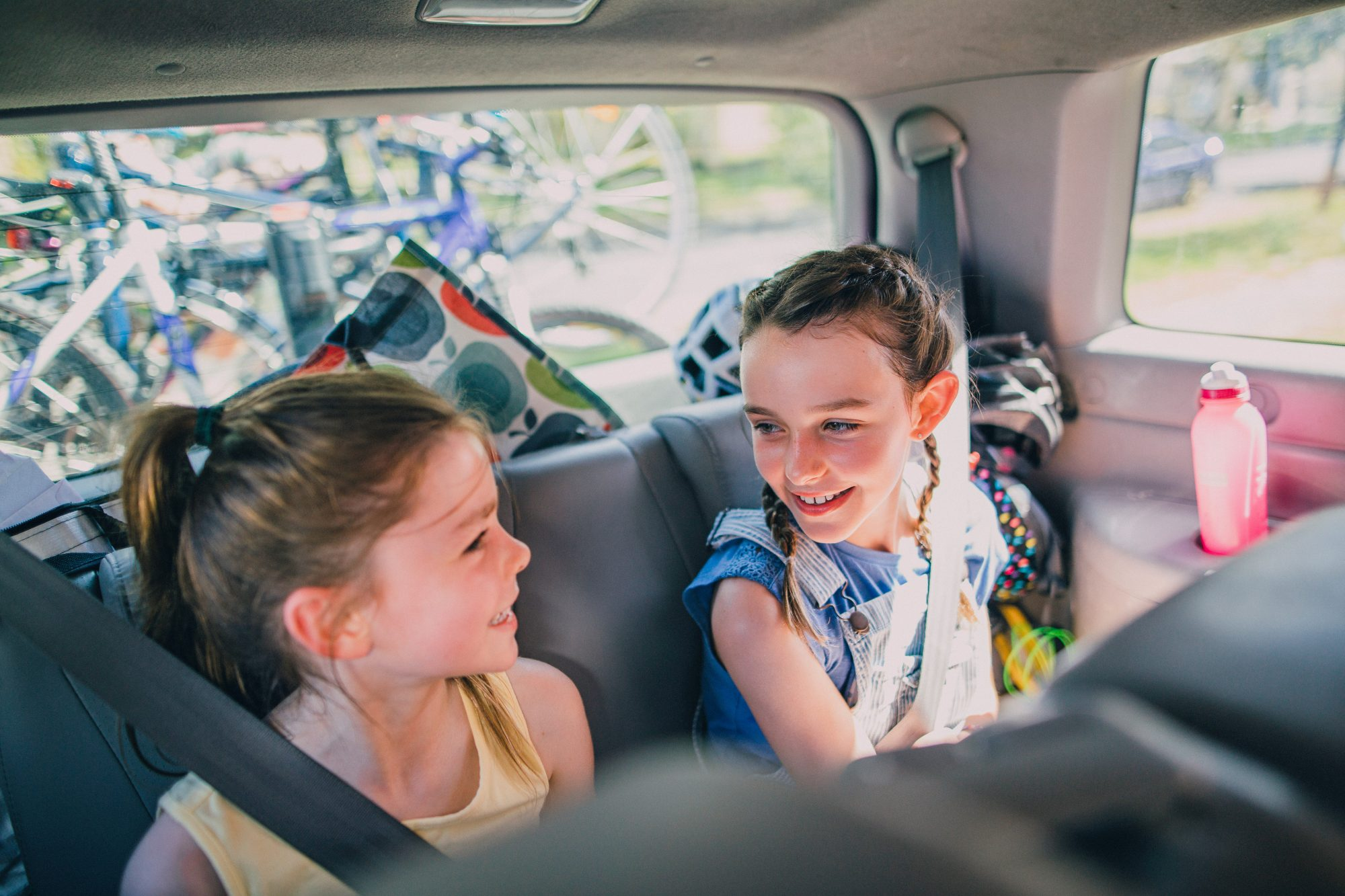 An image of two sisters sitting in a car on a road trip.