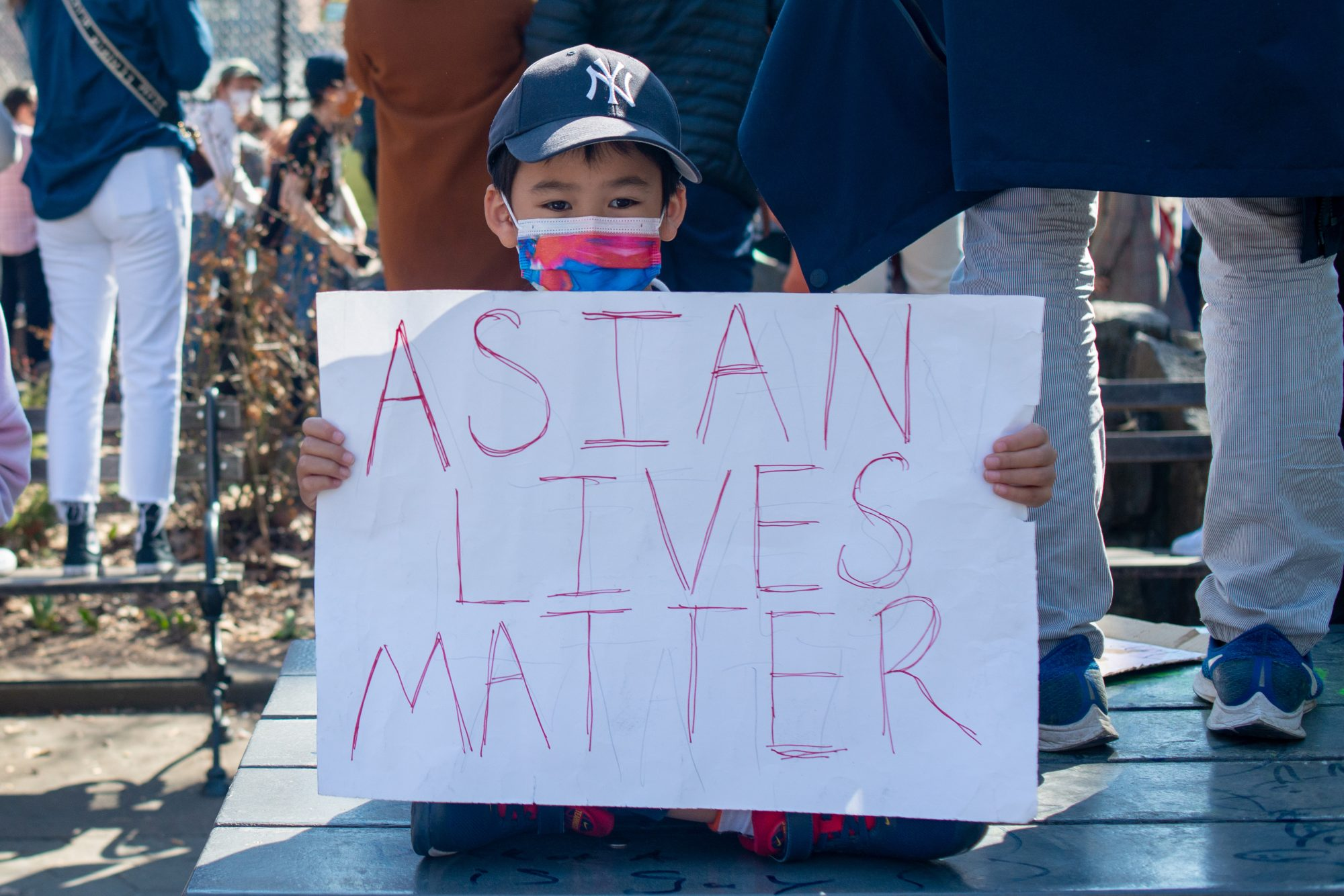 An image of a little boy holding an Asian Lives Matter sign at a protest.
