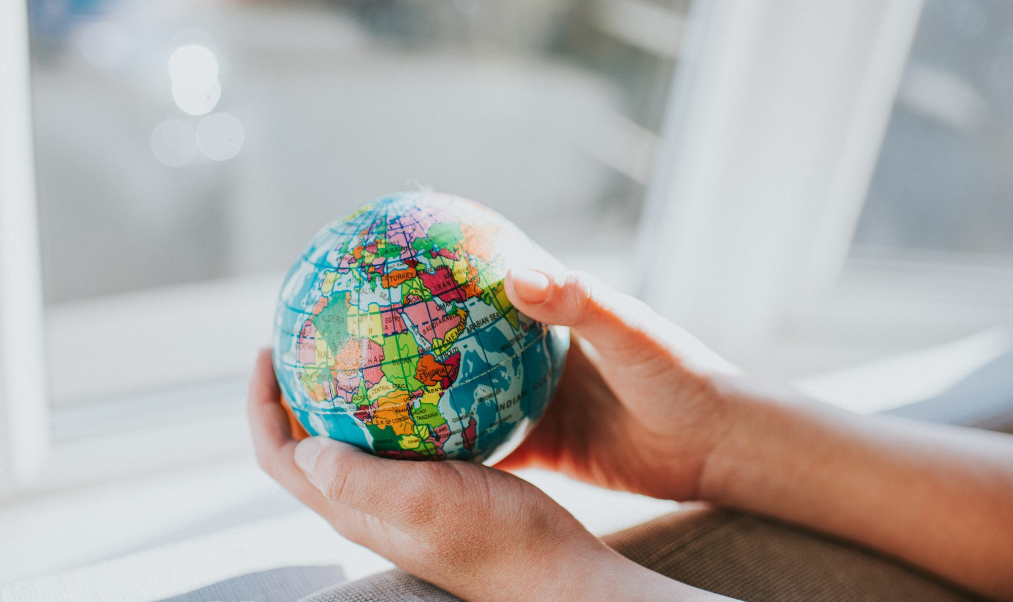 An image of a girl's hands holding a globe.