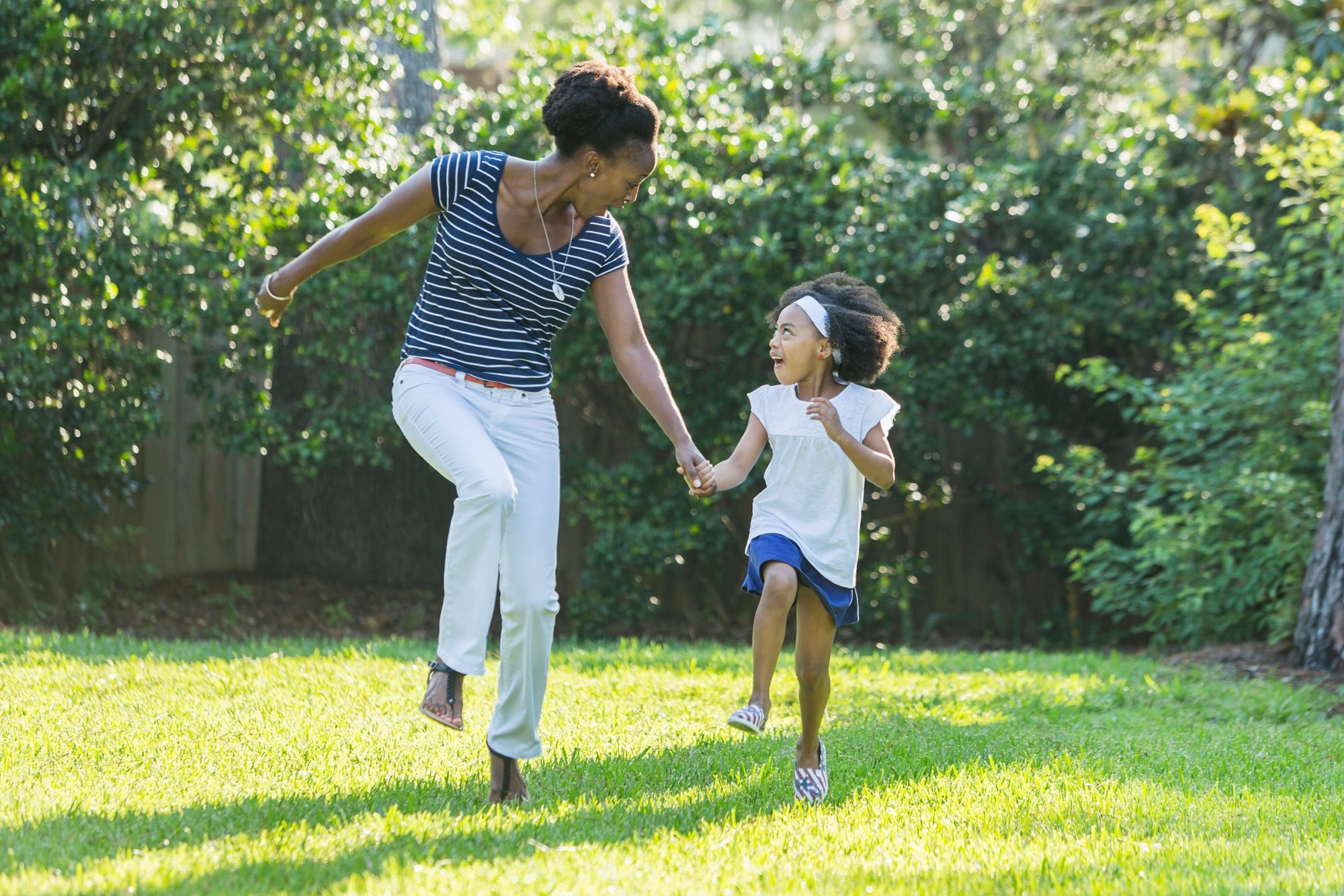 mother and daughter looking at each other while holding hands running through grass outside