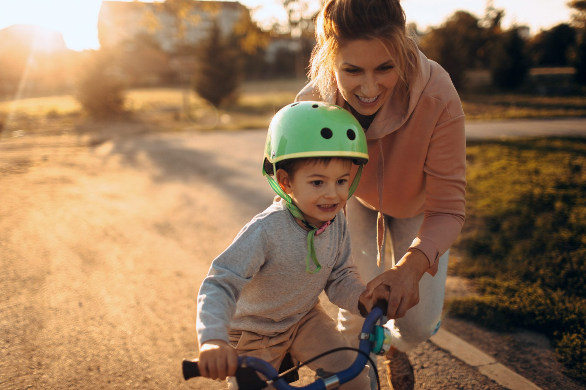 An image of a mom teaching her son to ride a bike.