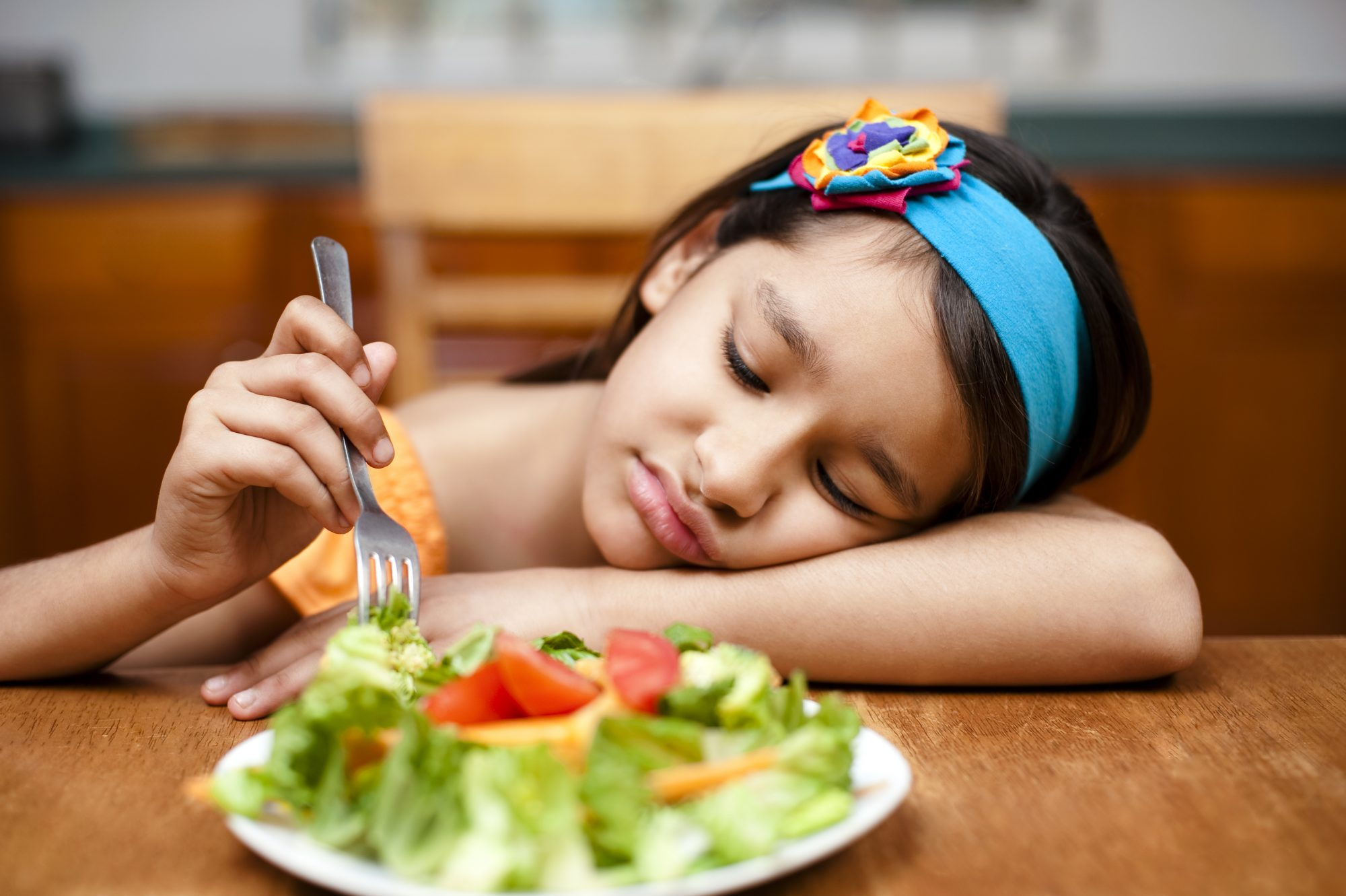 An image of a little girl sad at the dinner table.