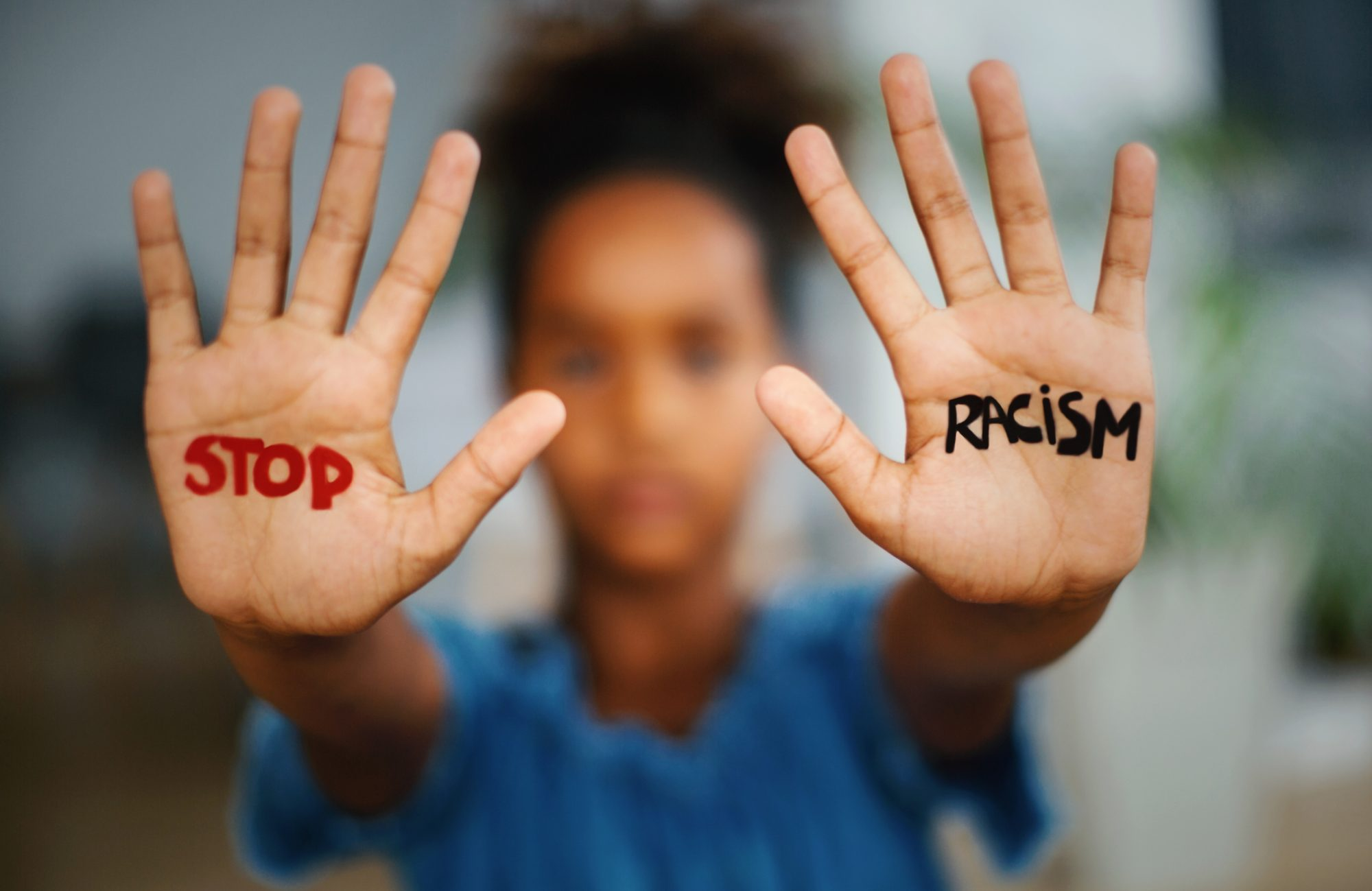 """An image of a child's hands that say """"Stop Racism""""."""