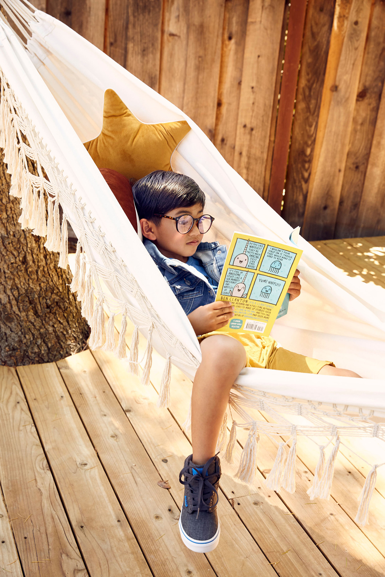 child reading a book in hammock