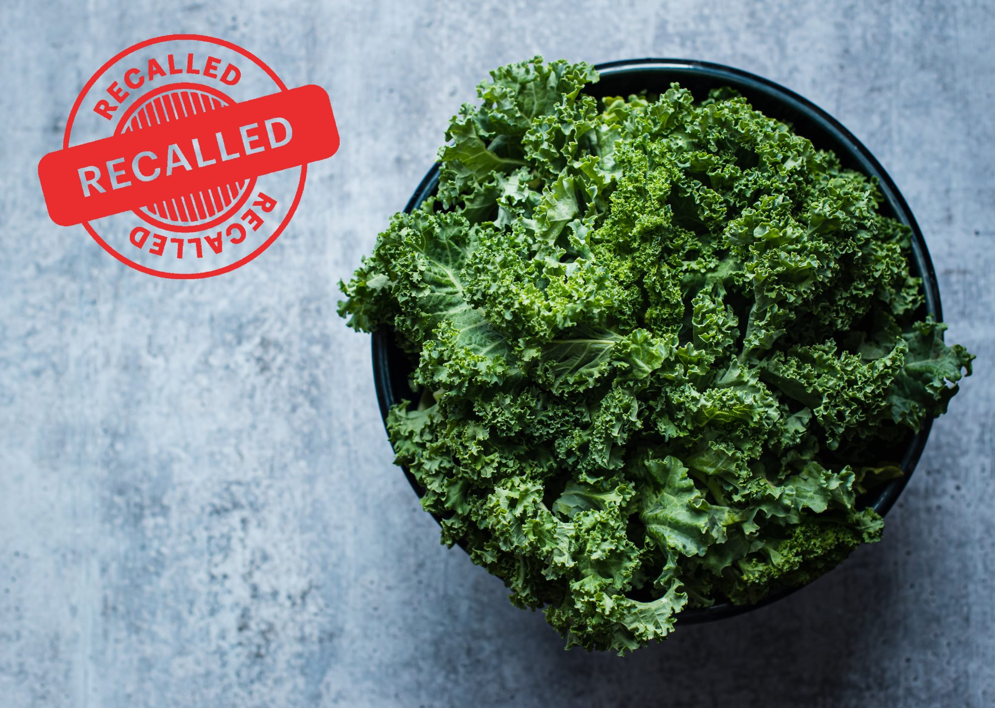 Overhead view of a bowl of kale against a gray cement counter with recall stamp