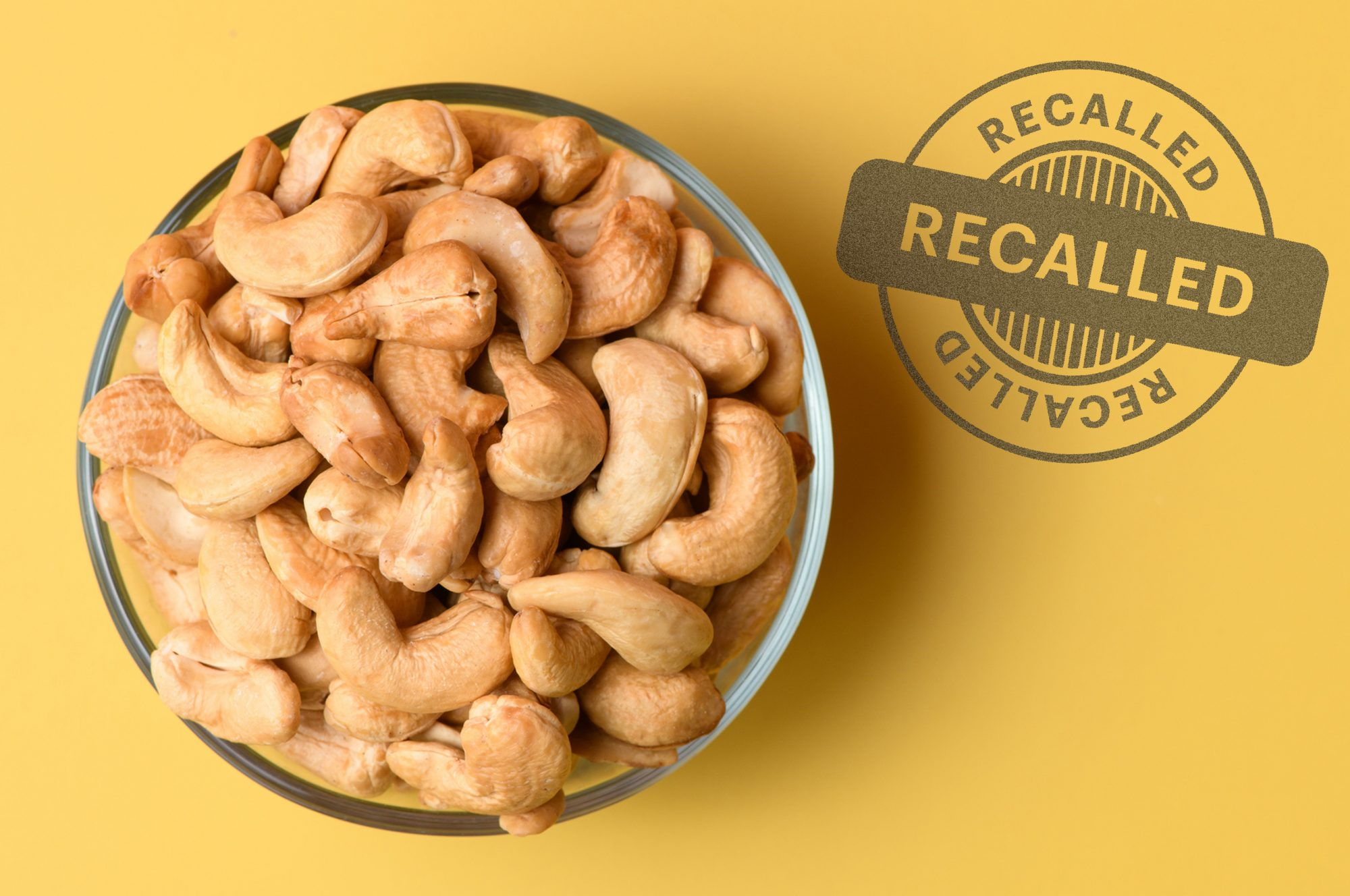 An image of cashews on a yellow background with a recall sticker on it.