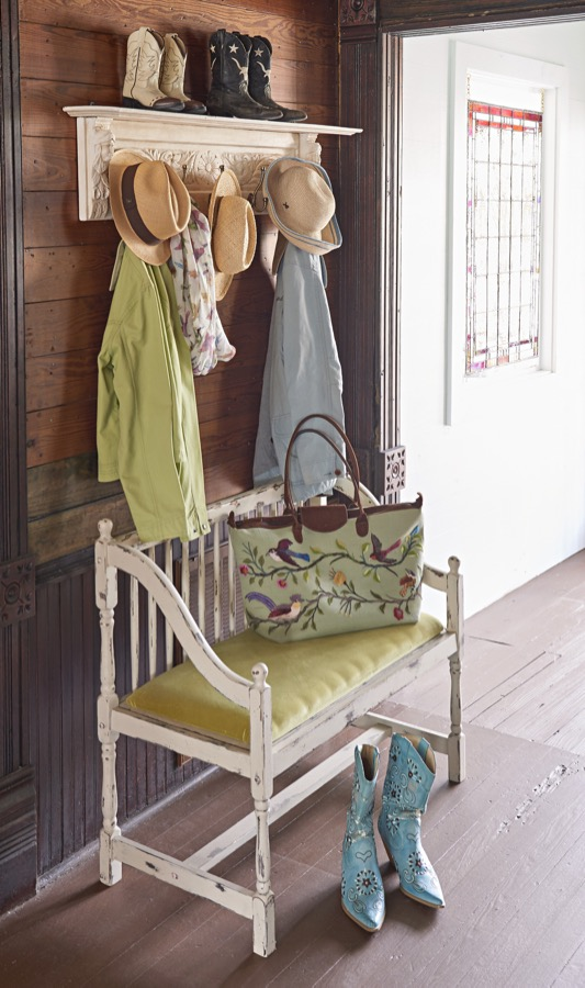 A vintage bench under coat hooks creates mudroom space.