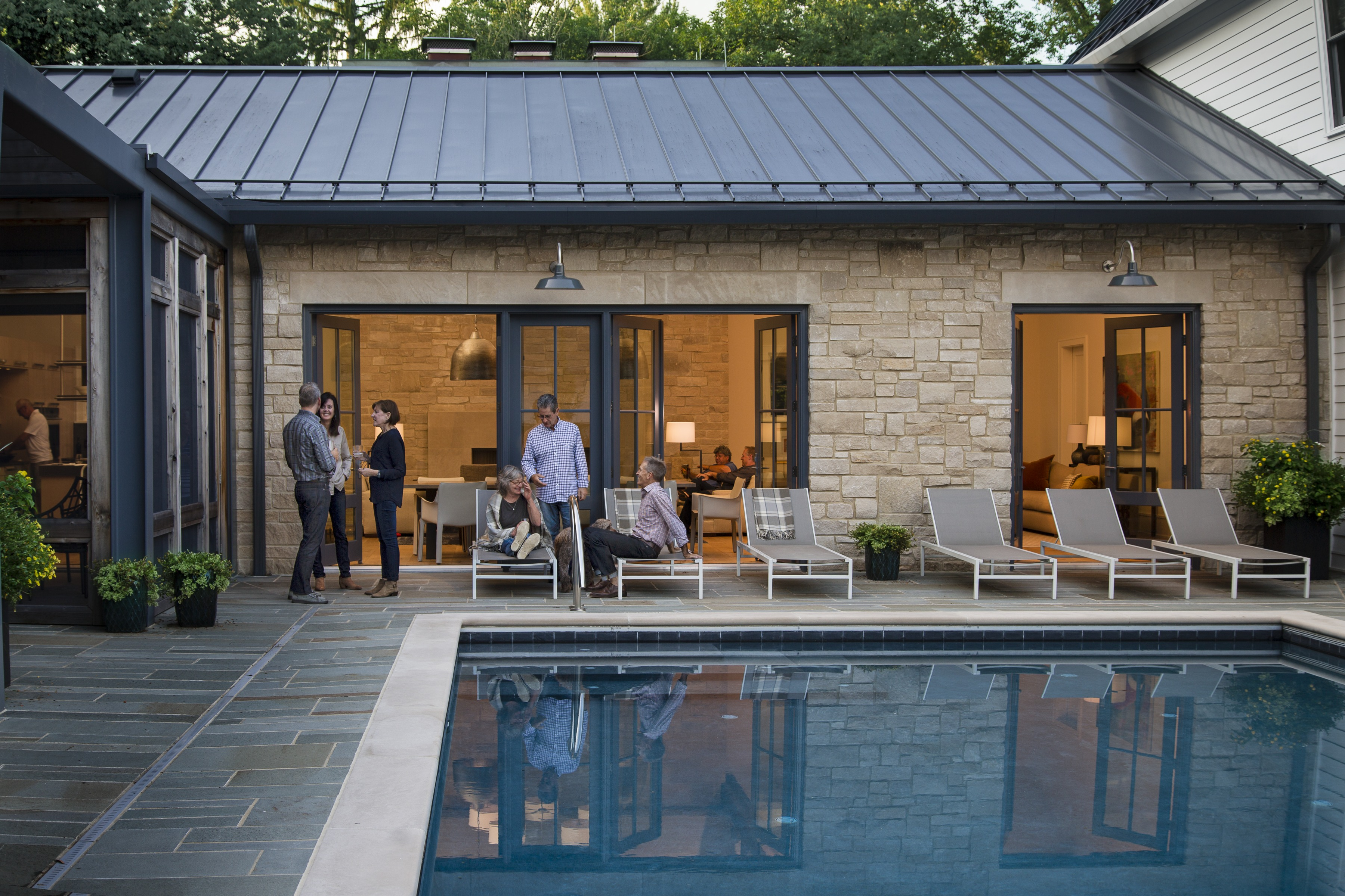 The home features a limestone breezeway (and great-room) that connects two clapboard structures. Together, the three sides frame a secluded patio.