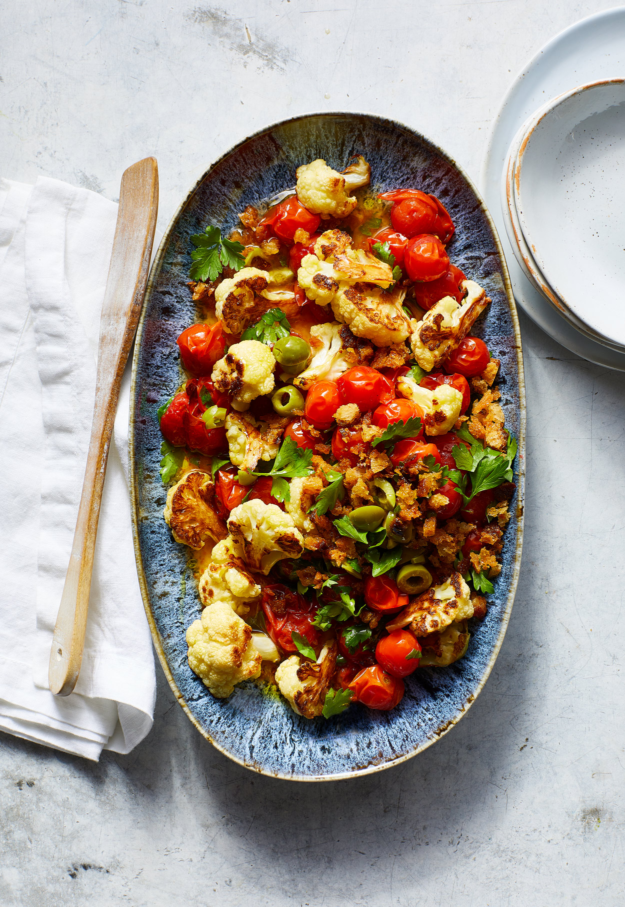oval dish of Roasted Cauliflower and Tomatoes with Olives and Garlic Breadcrumbs