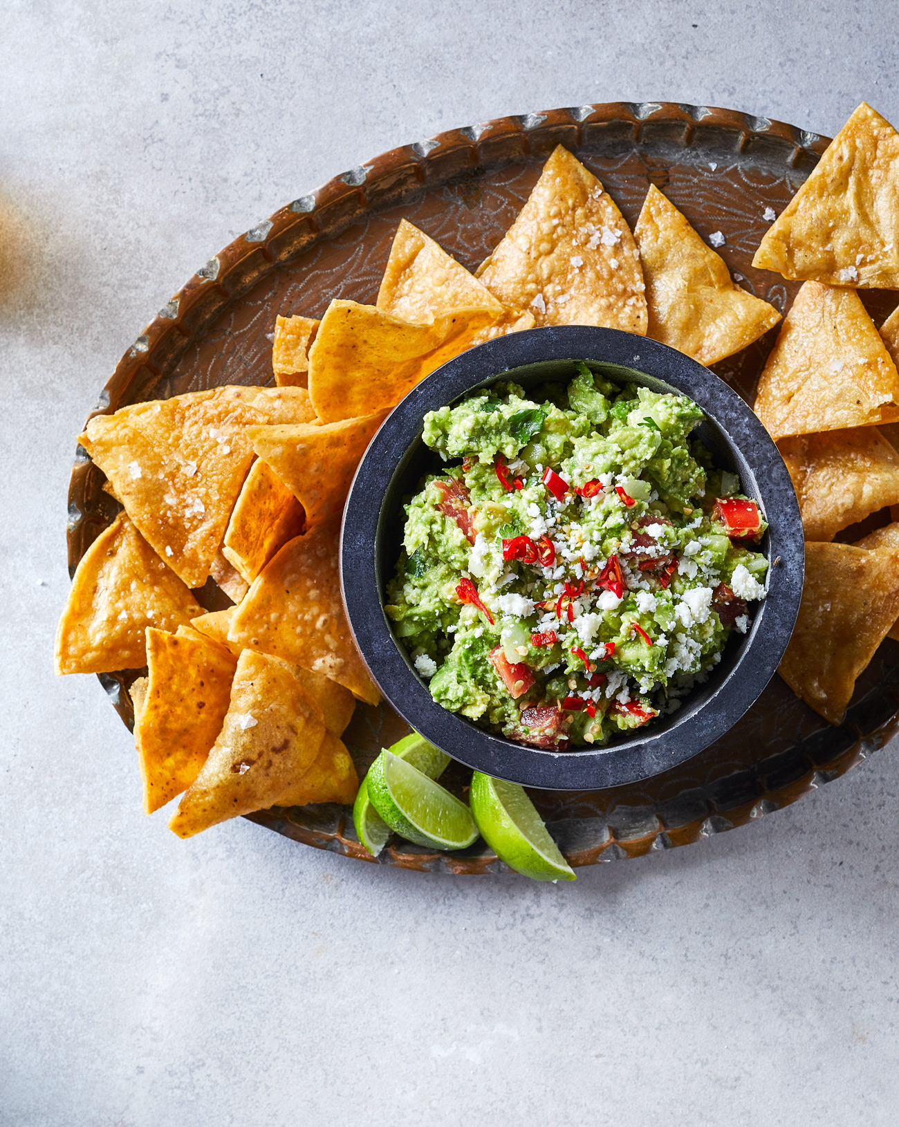 bowl of Mariana's Guacamole on platter with chips