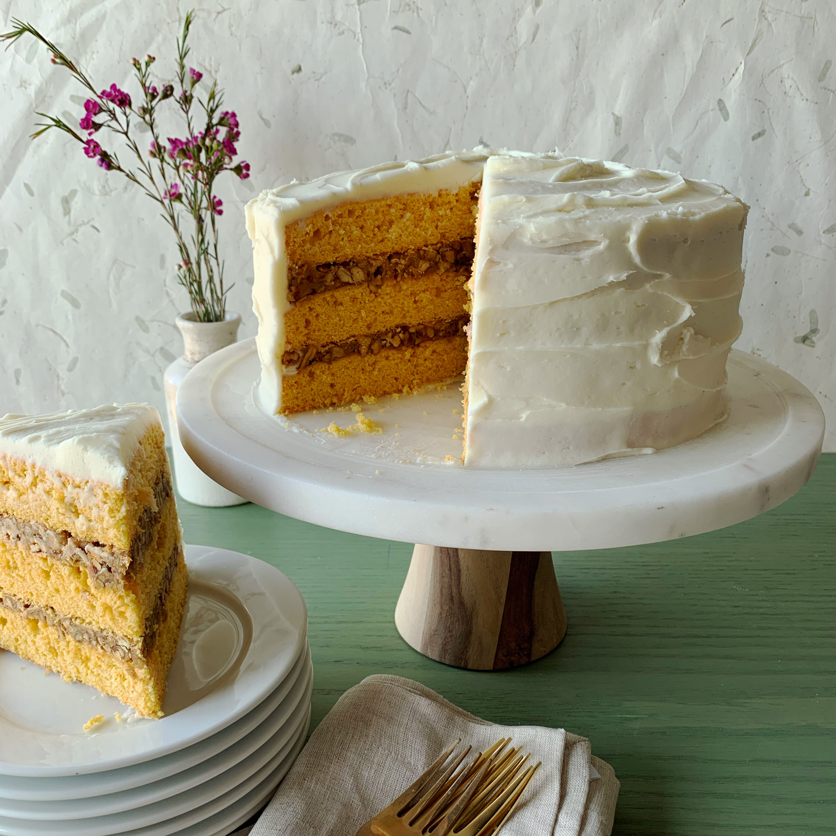 Carrot-Spice Cake with Coconut-Pecan Filling on cake stand piece on plate