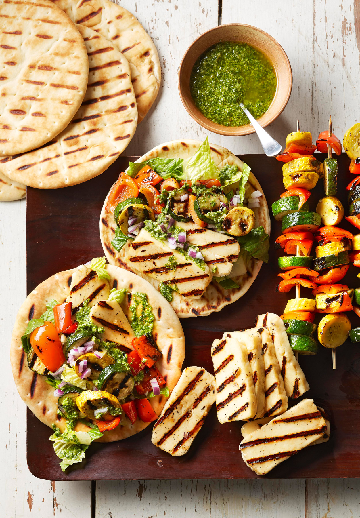 Pesto Veggie Gyros on wooden platter with grilled chicken and kabobs