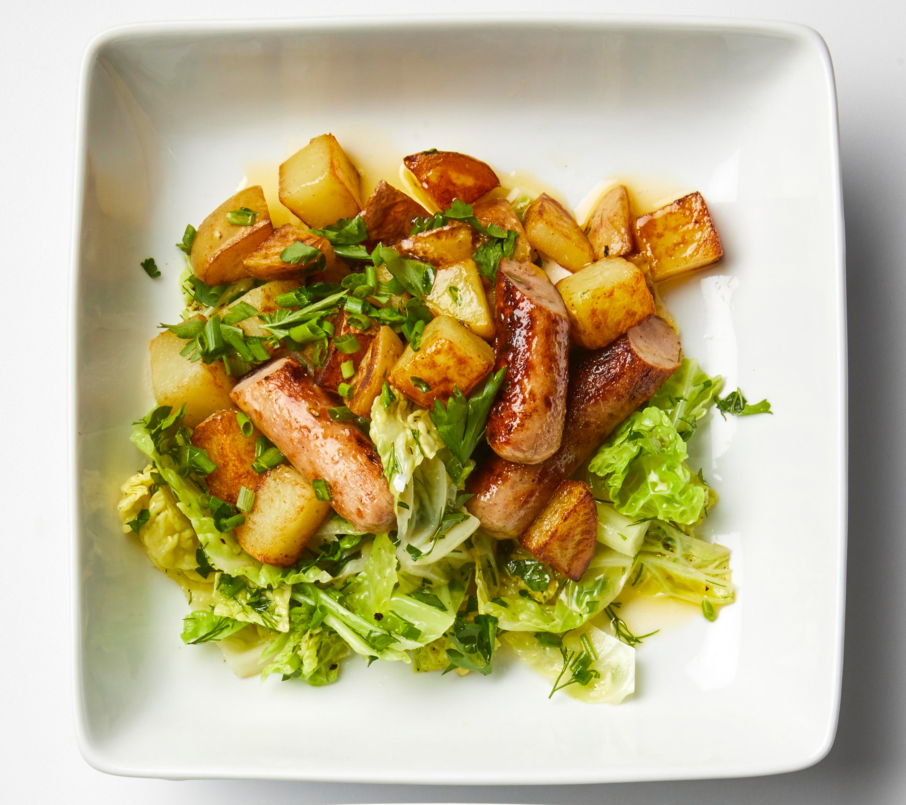 square white plate of Sausage with Skillet Potatoes and Buttered Cabbage
