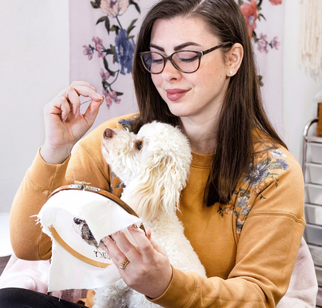 Michelle Staub doing embroidery with dog on lap