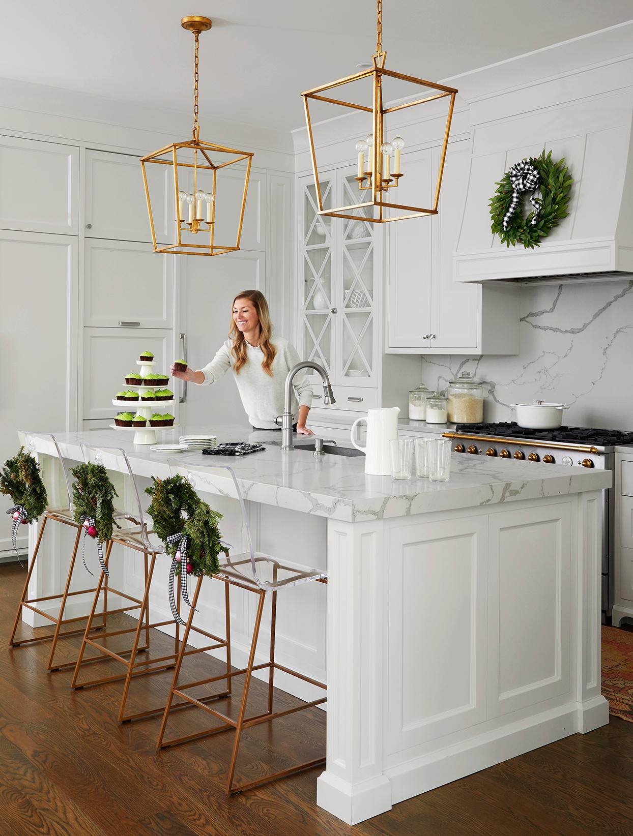 woman white modern kitchen gold pendants