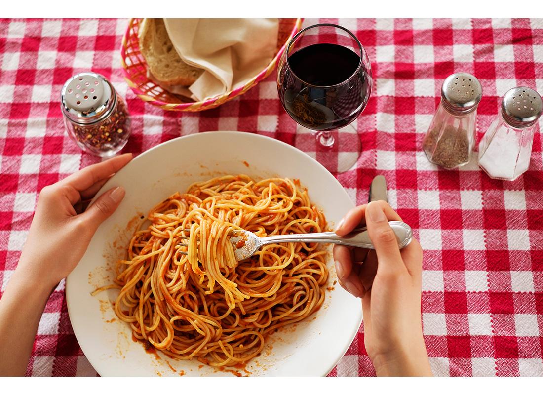 woman eating bowl of pasta