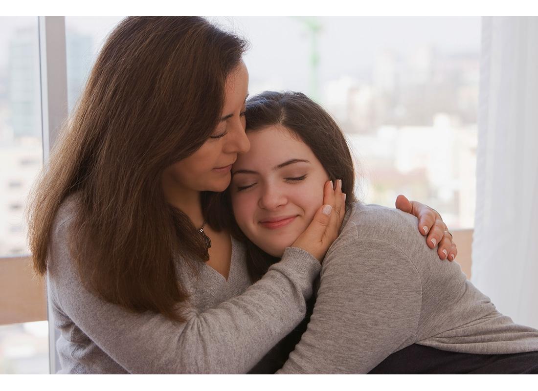 mom hugging teen daughter gray sweaters