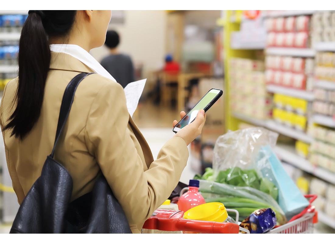 woman grocery shopping with phone and paper list
