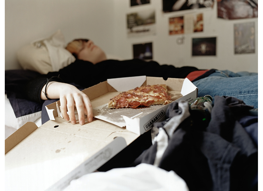 Boy sleeping with pizza on bed