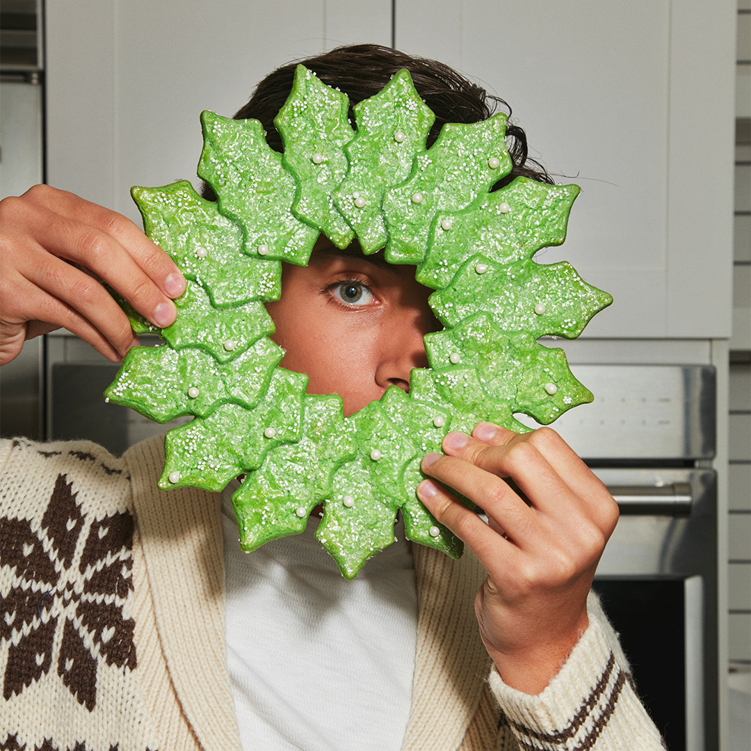 girl holding holiday wreath cookie in front of her face