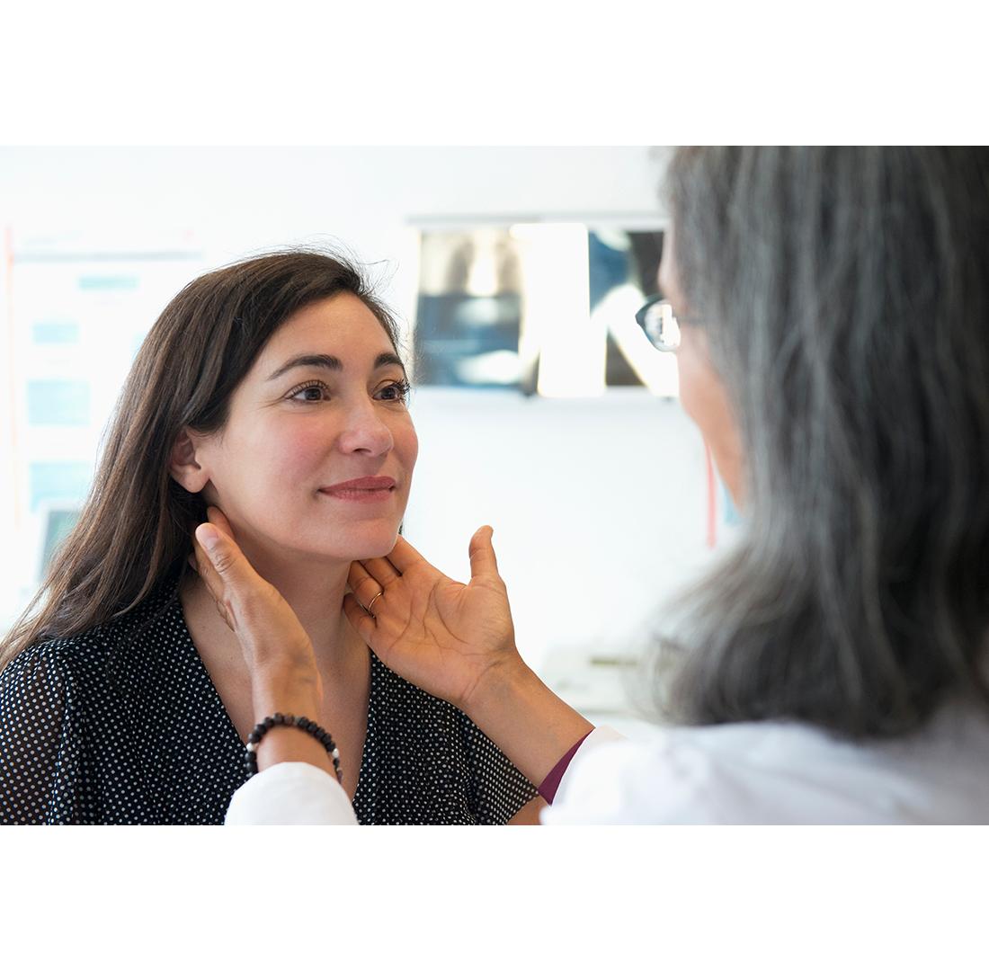 doctor touching woman's throat
