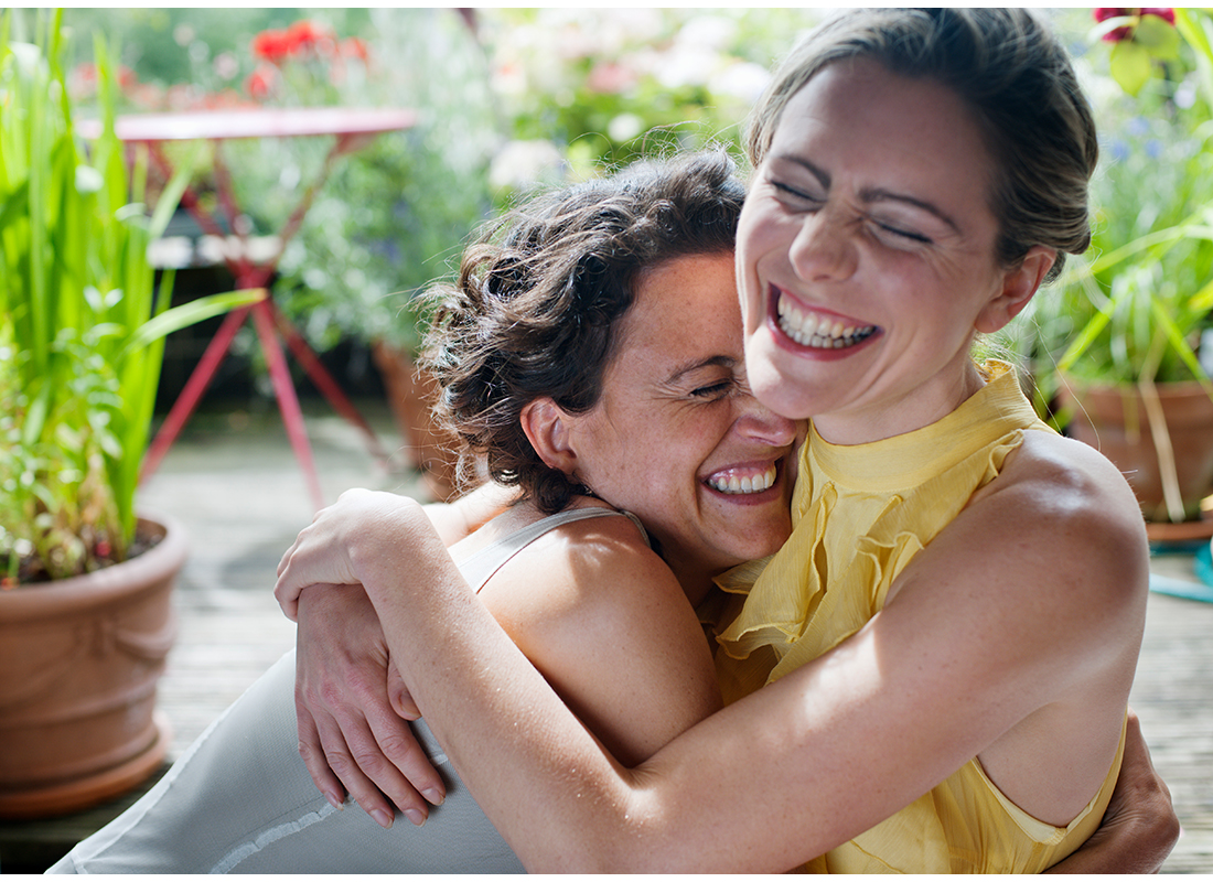 two women happily hugging