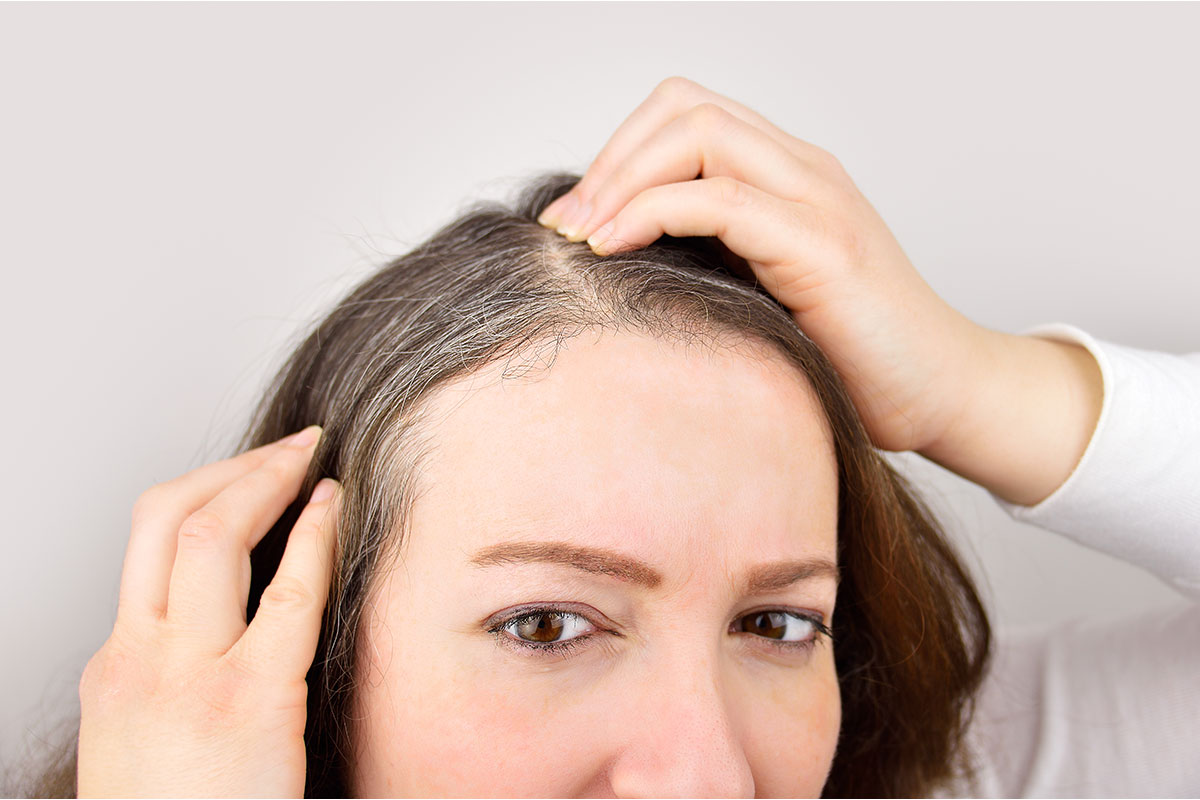 woman looking at her gray roots