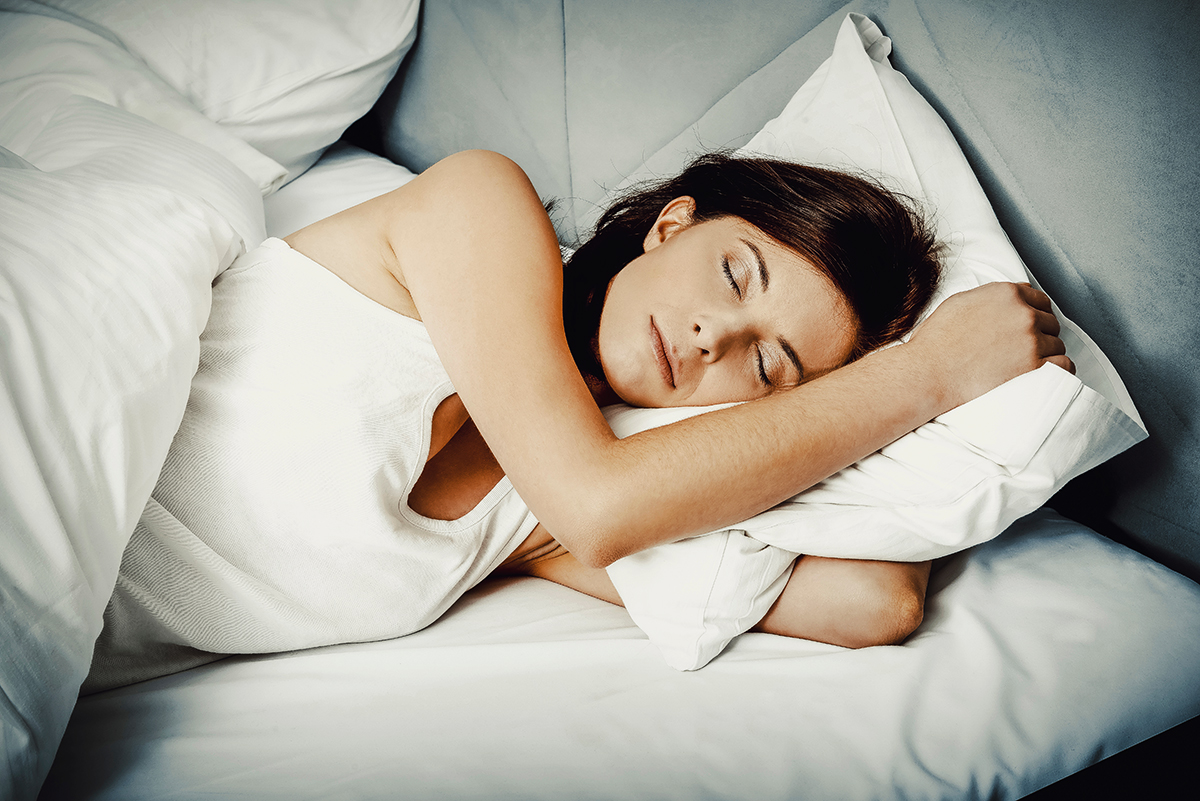 woman sleeping in bed with white linens
