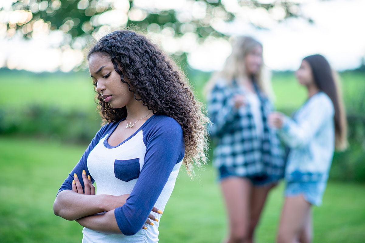 Two teen girls in the background making fun of or bullying a third girl