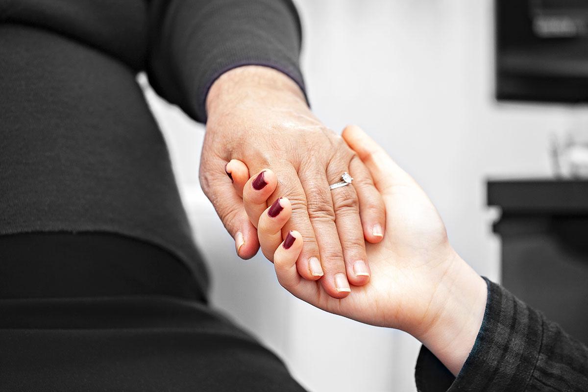 anonymous women holding hands alzheimers
