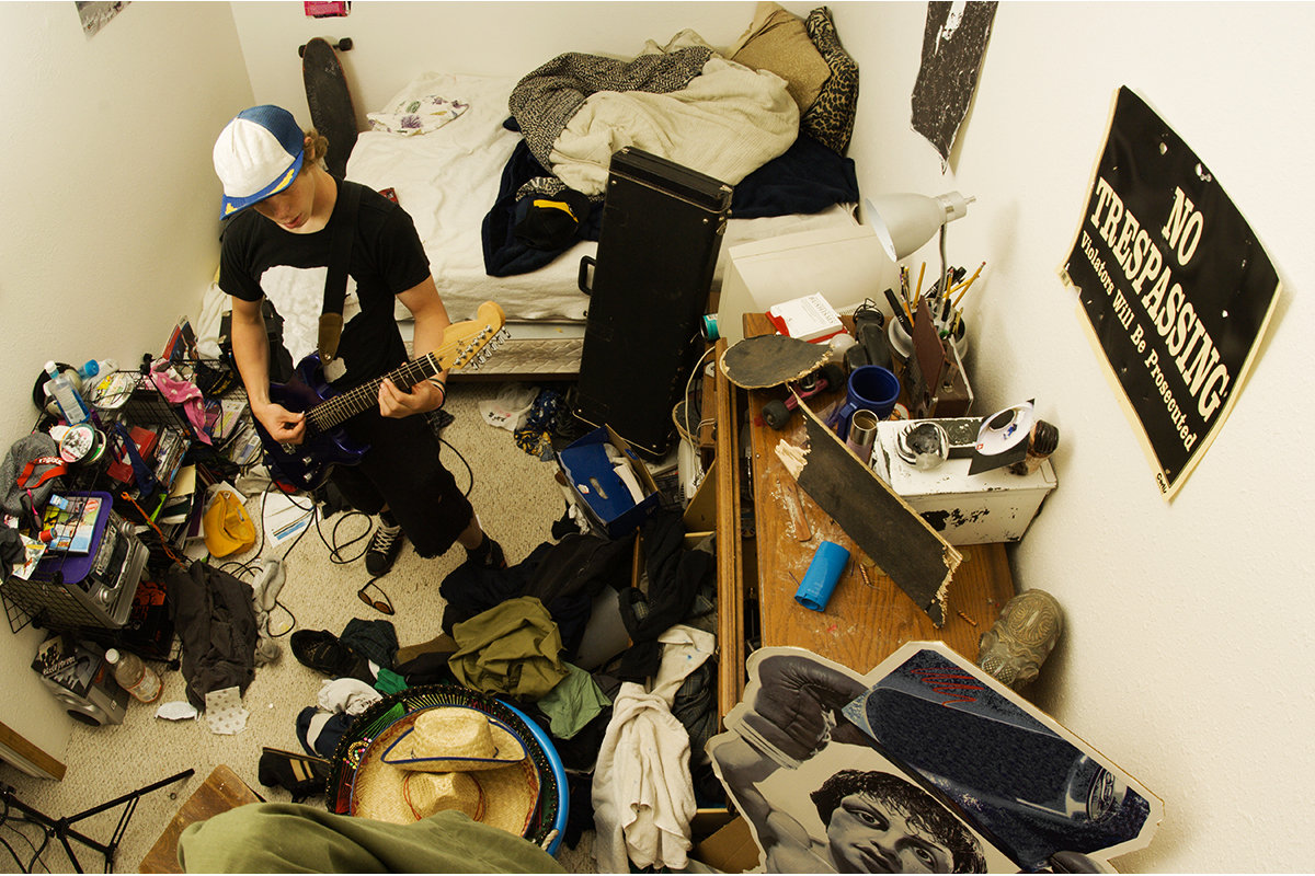 teen playing guitar in extremely messy bedroom