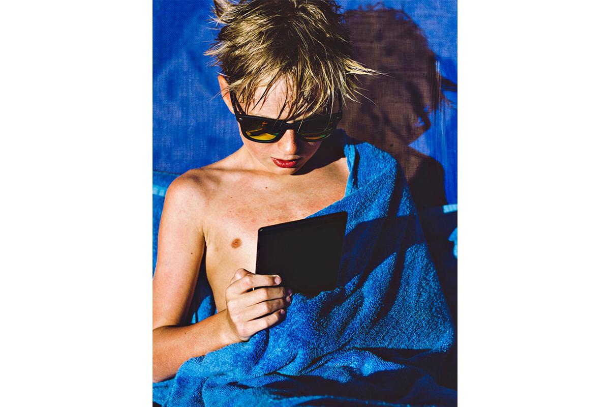 boy reading on amazon kindle paperwhite