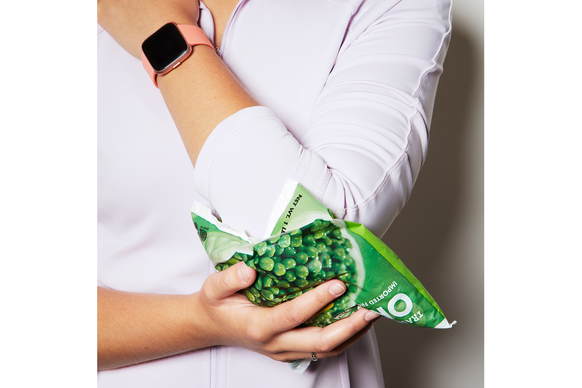 Girl icing her elbow with a bag of frozen peas