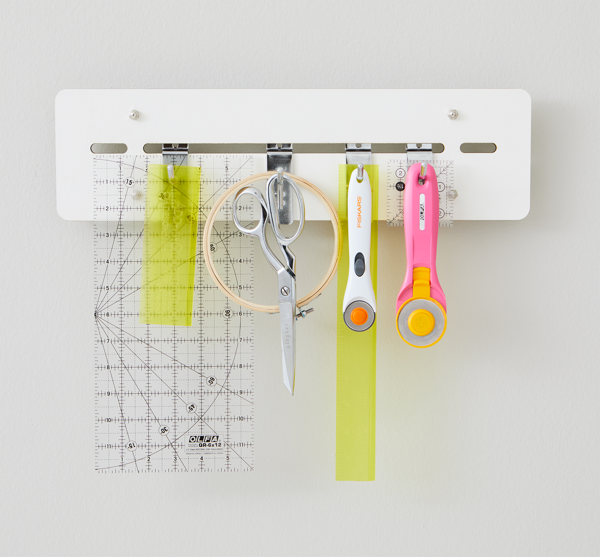 "What: Organize rulers, cutters, and other supplies with an 18""-long wall rack that can hold up to 28 rulers on four adjustable hooks.                                       Price: $35.99                                       For more info: rrrulerrack.com"