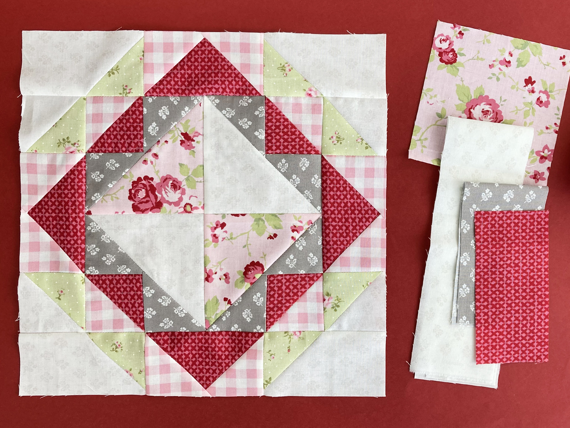 Red, pink, green, and gray floral quilt block with fabrics to the side.