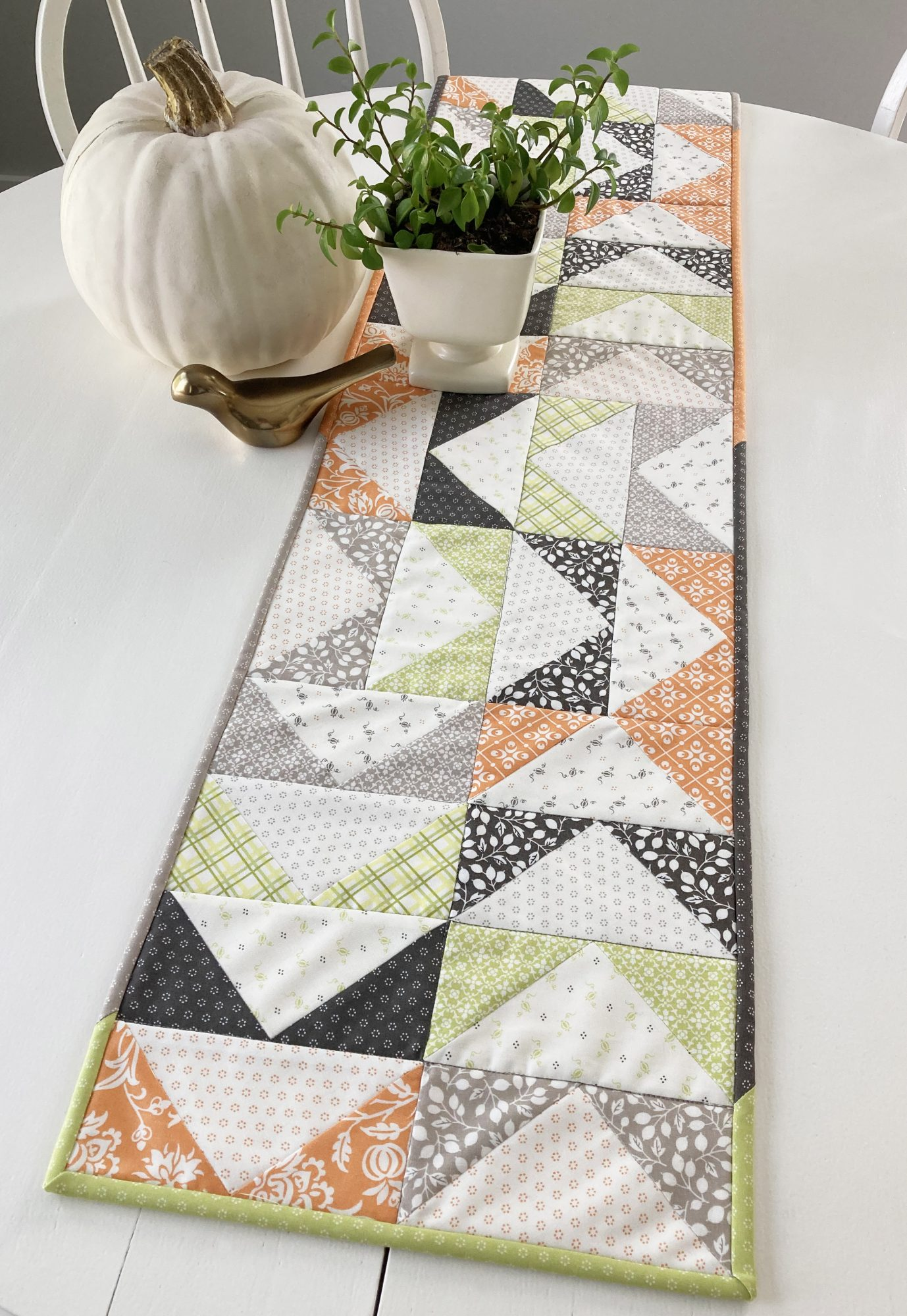 Flying geese table runner made in orange, green, and gray fall prints.
