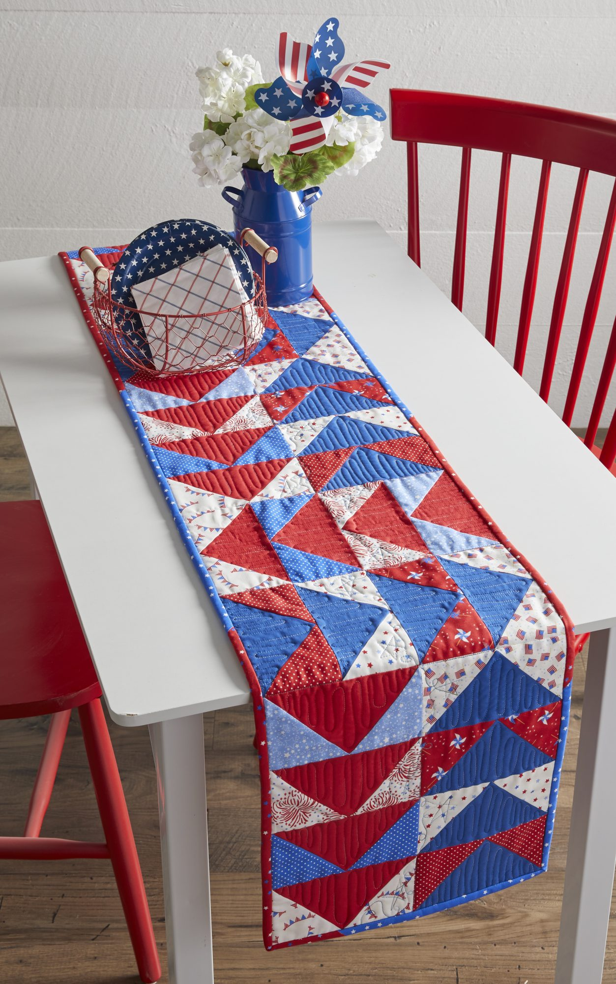 Flying geese table runner made with red, white, and blue fabrics on table with patriotic accessories