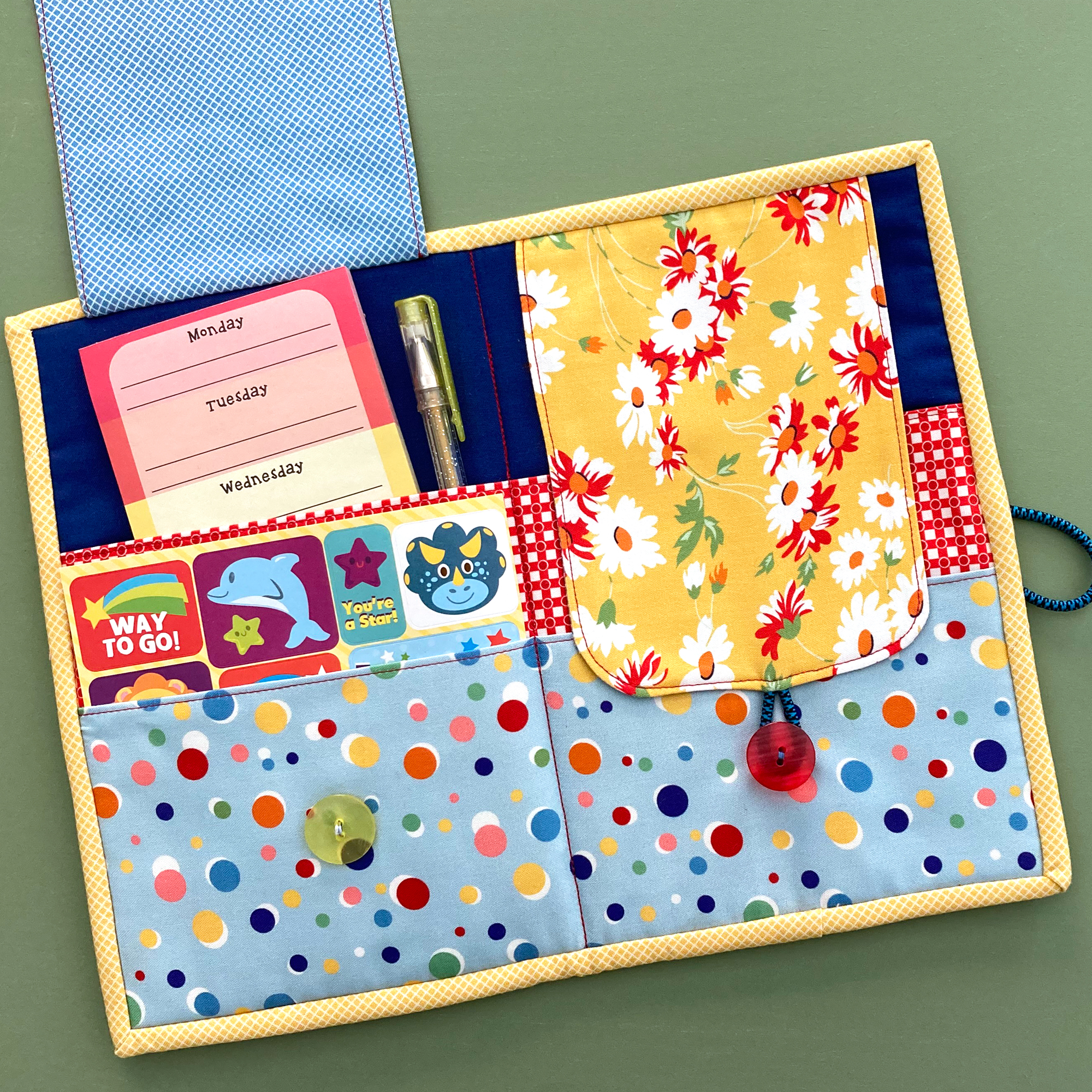Open fabric organizer with stickers, notepad and pen.