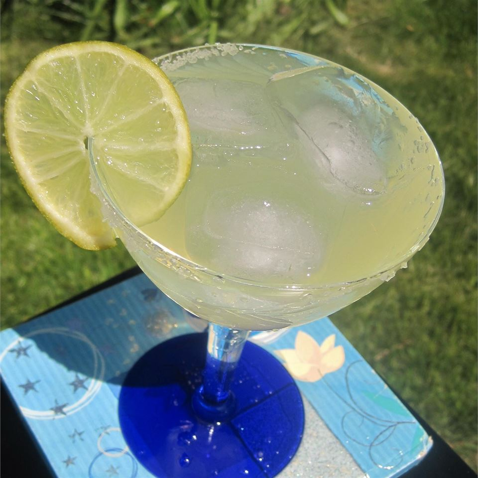 a margarita on the rocks in a fiesta glass with a lime garnish