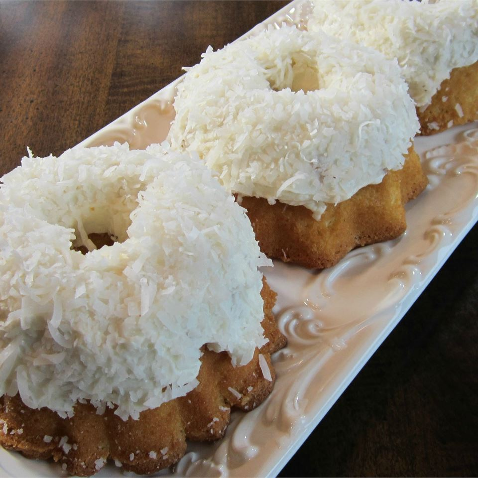 A rectangular tray holding mini bundt cakes topped with white frosting and shredded coconut